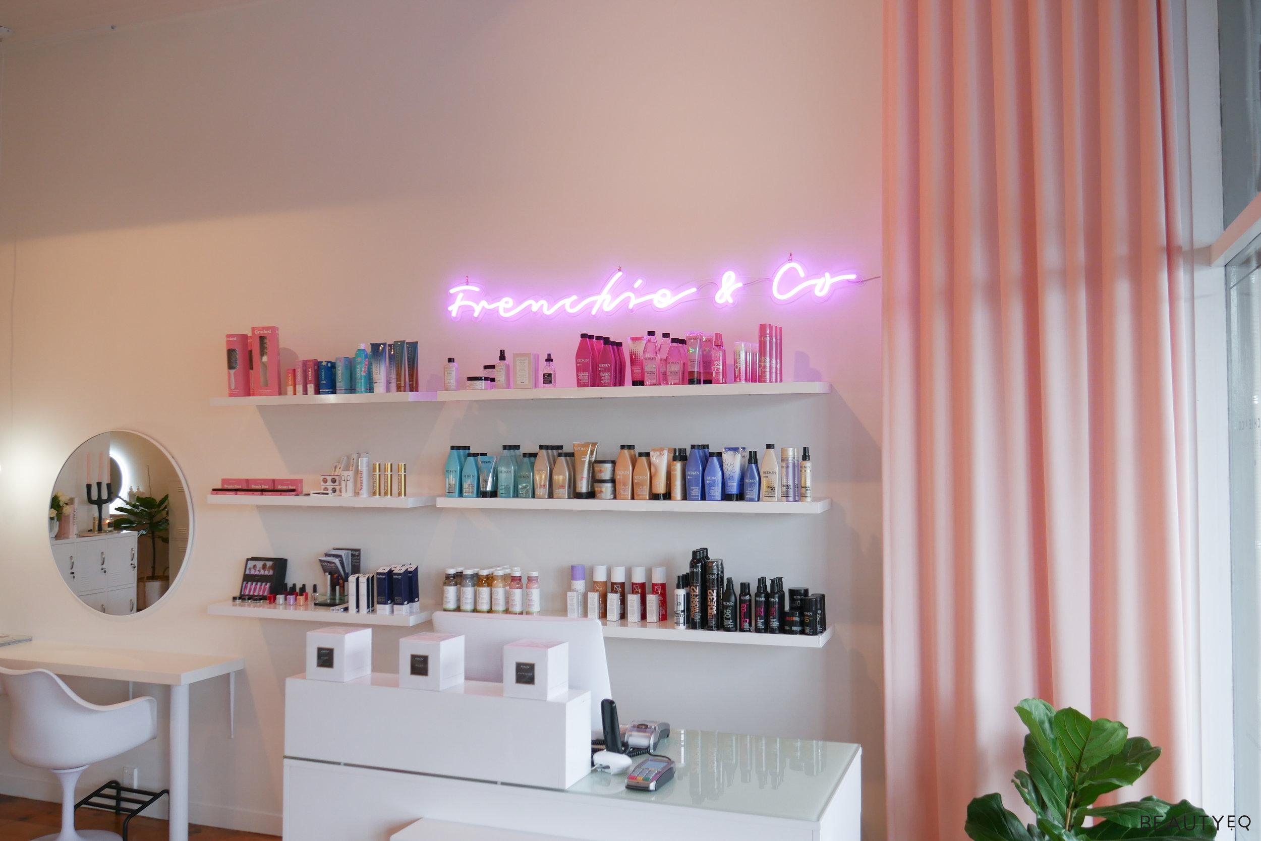 A beauty salon with various beauty products lines up on three different shelves and a neon light above them saying 'Frenchie & Co'