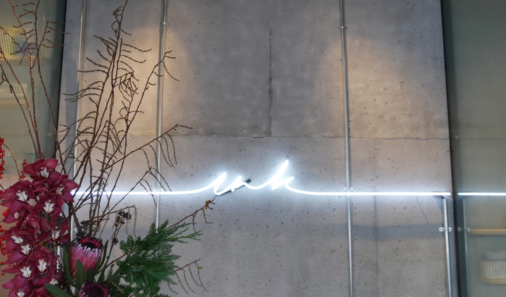 A grey concrete wall with a neon light across it and a pink floral arrangement in the corner