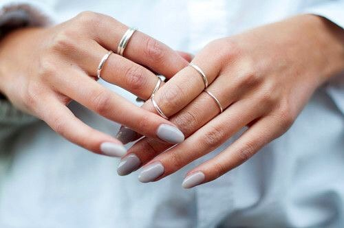 Slim hands with cloudy blue coloured nails holding each other and dainty silver rings on the fingers