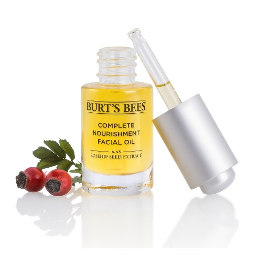 An open bottle of Burt's Bees complete nourishment facial oil with a silver lid leaning on it and a red plant next to it