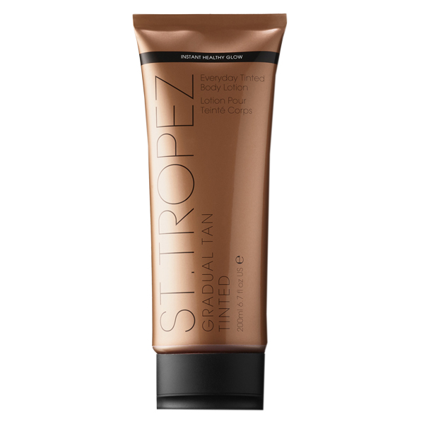 ST Tropez tinted body lotion in a bronze bottle sitting on a black lid