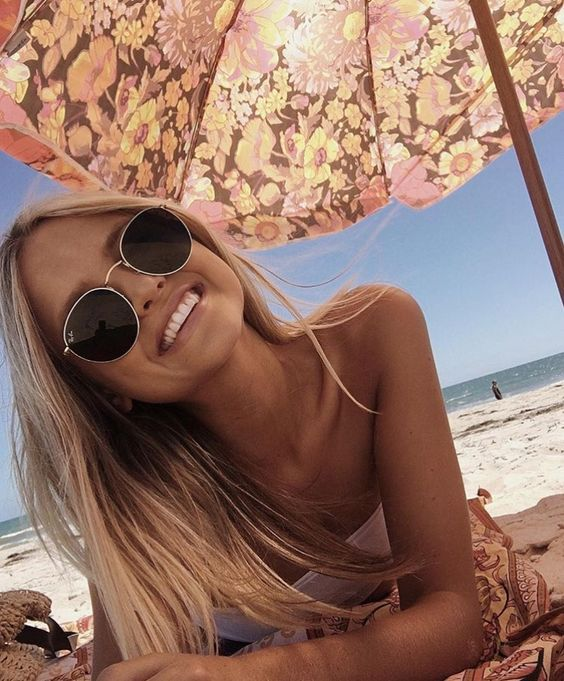 Blonde girl sitting on a beach under and umbrella wearing Ray Bans and smiling