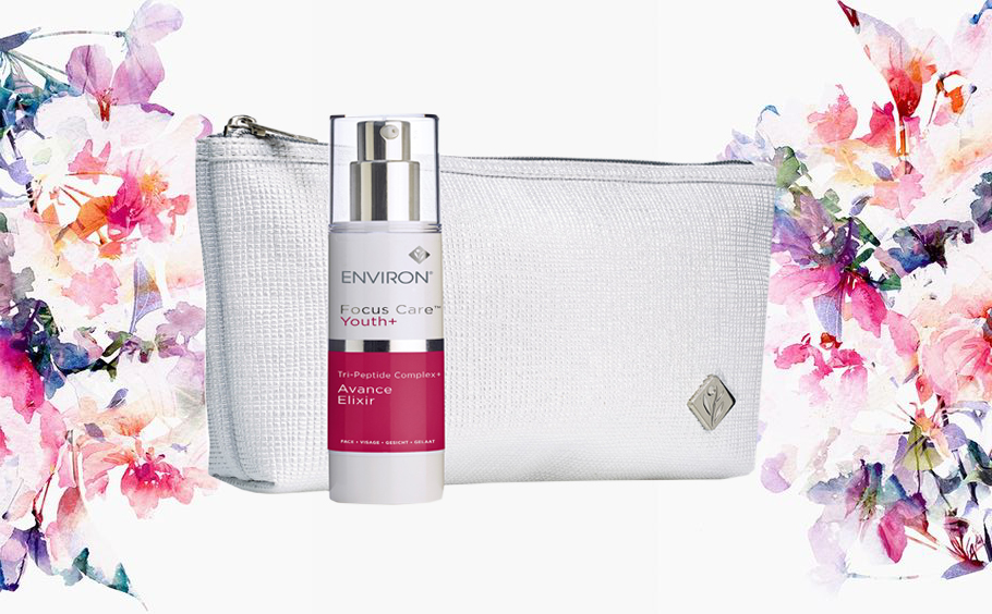 Environ beauty products in white and pink bottle placed in front of a white toiletries bag surrounded by floral died pattered