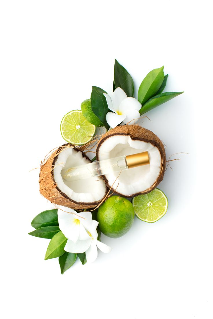 A coconut cracked open with a slim clear beauty product inside surrounded by flowers and slices of lime