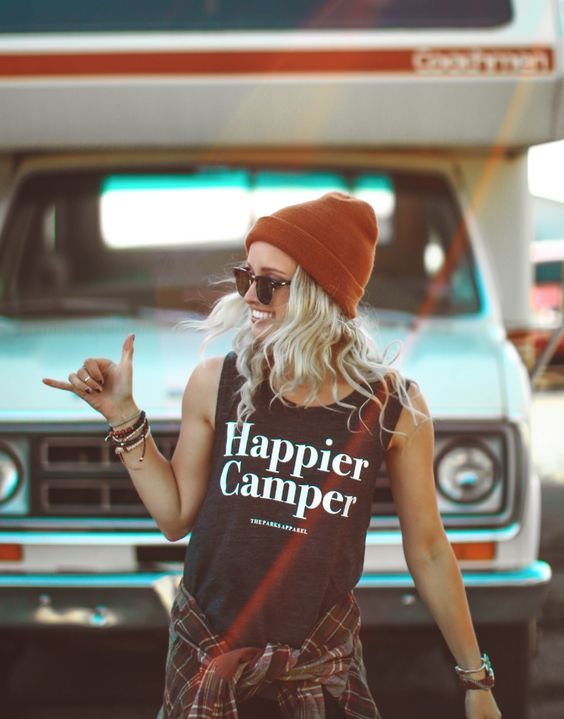 A blonde girl wearing an orange beanie and 'Happier Camper' tank top with a plaid shirt wrapped around her waist, pulling the 'shakka' sign infront of a blue car