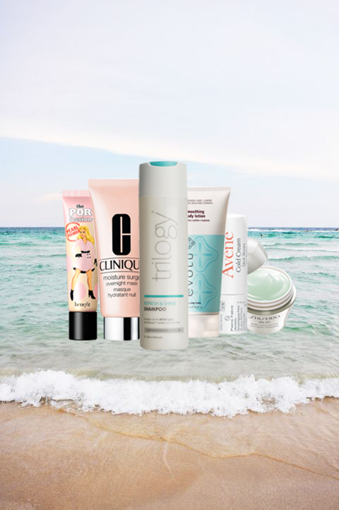 A range of different beauty products arranged against a seashore background