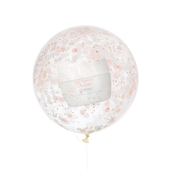 A translucent balloon with light pink and white circular patterns on it floating with a string attached to it and an Avene skin product held inside it