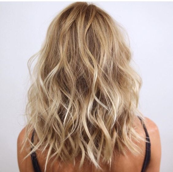 the back of a blonde woman's hair with messy waves