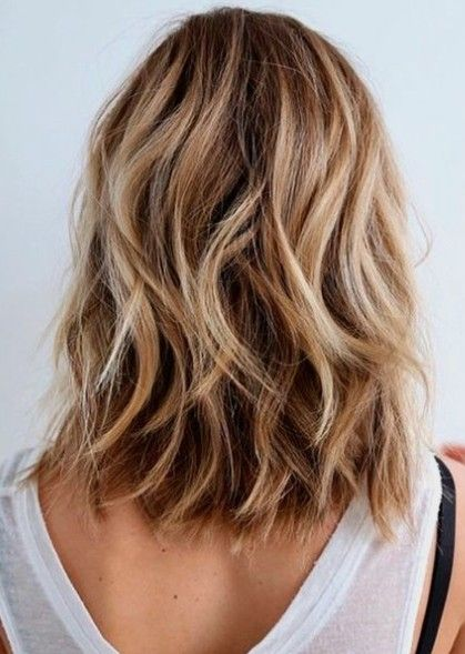 The back of a blonde woman's head with waves