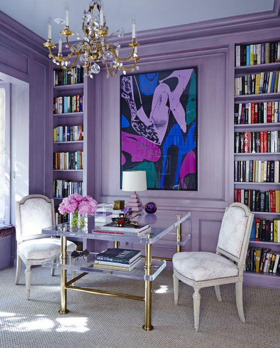 Purple room with purple walls, art on wall and book shelves/library
