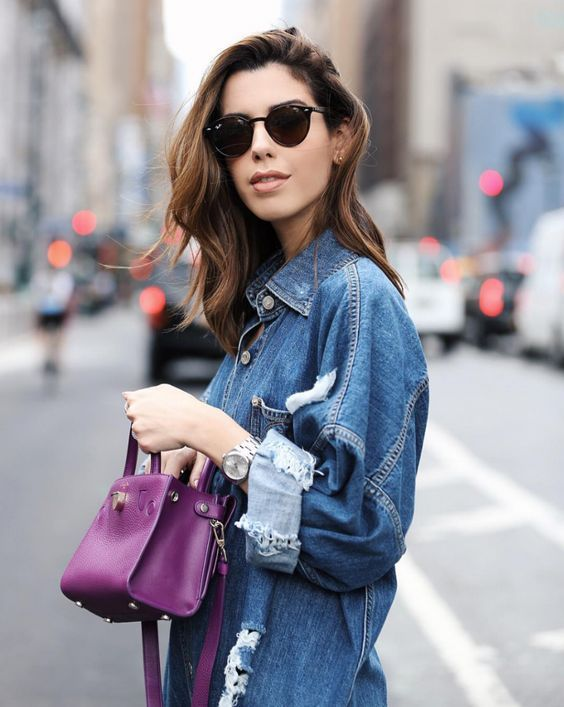 Woman in blue denim jacket holding purple bag