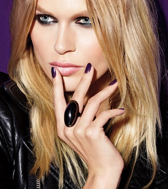 Blonde model face with hand on lips, wearing dark purple nail polish