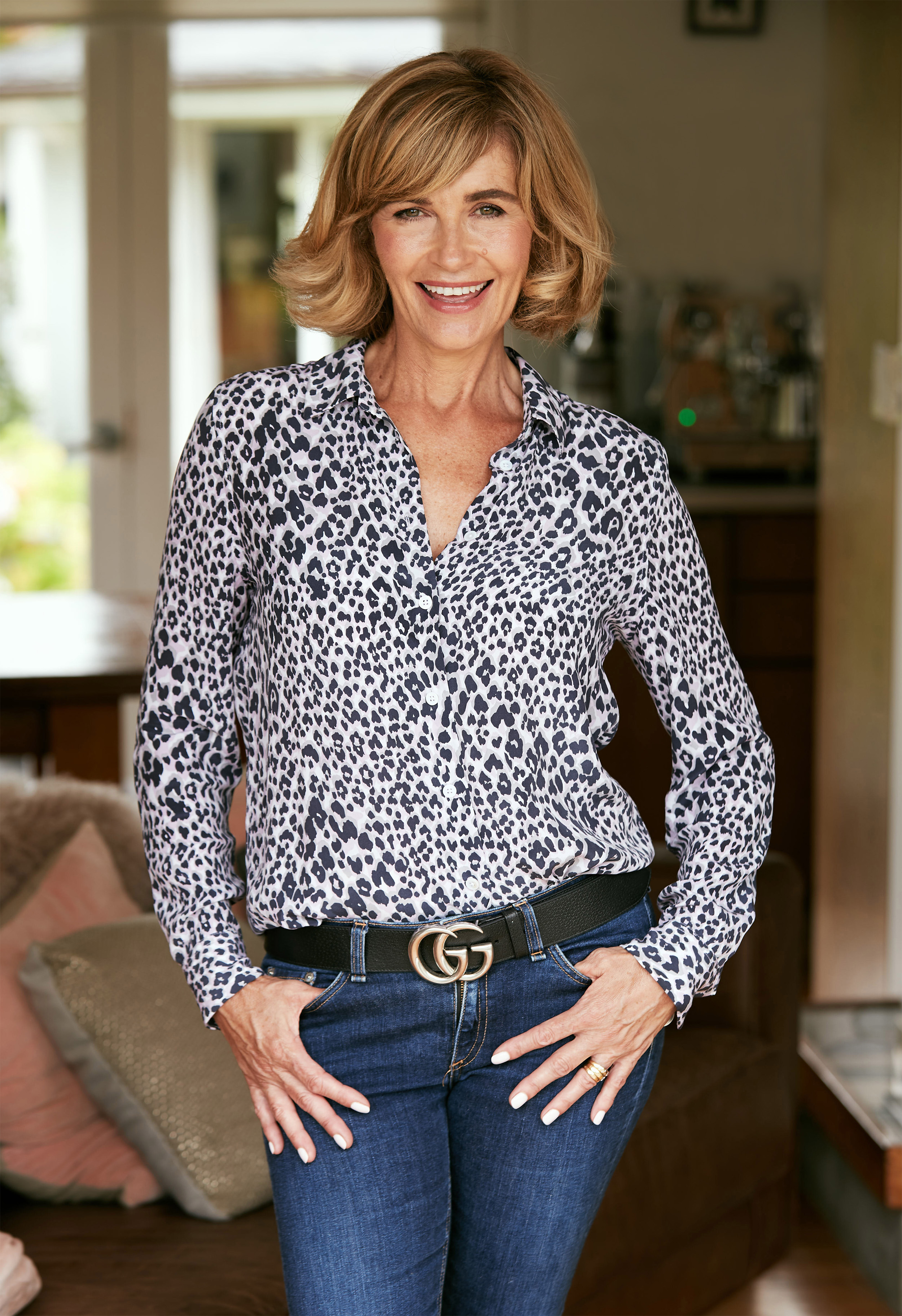Blonde lady wearing leopard print shirt and gucci belt with hands in pockets