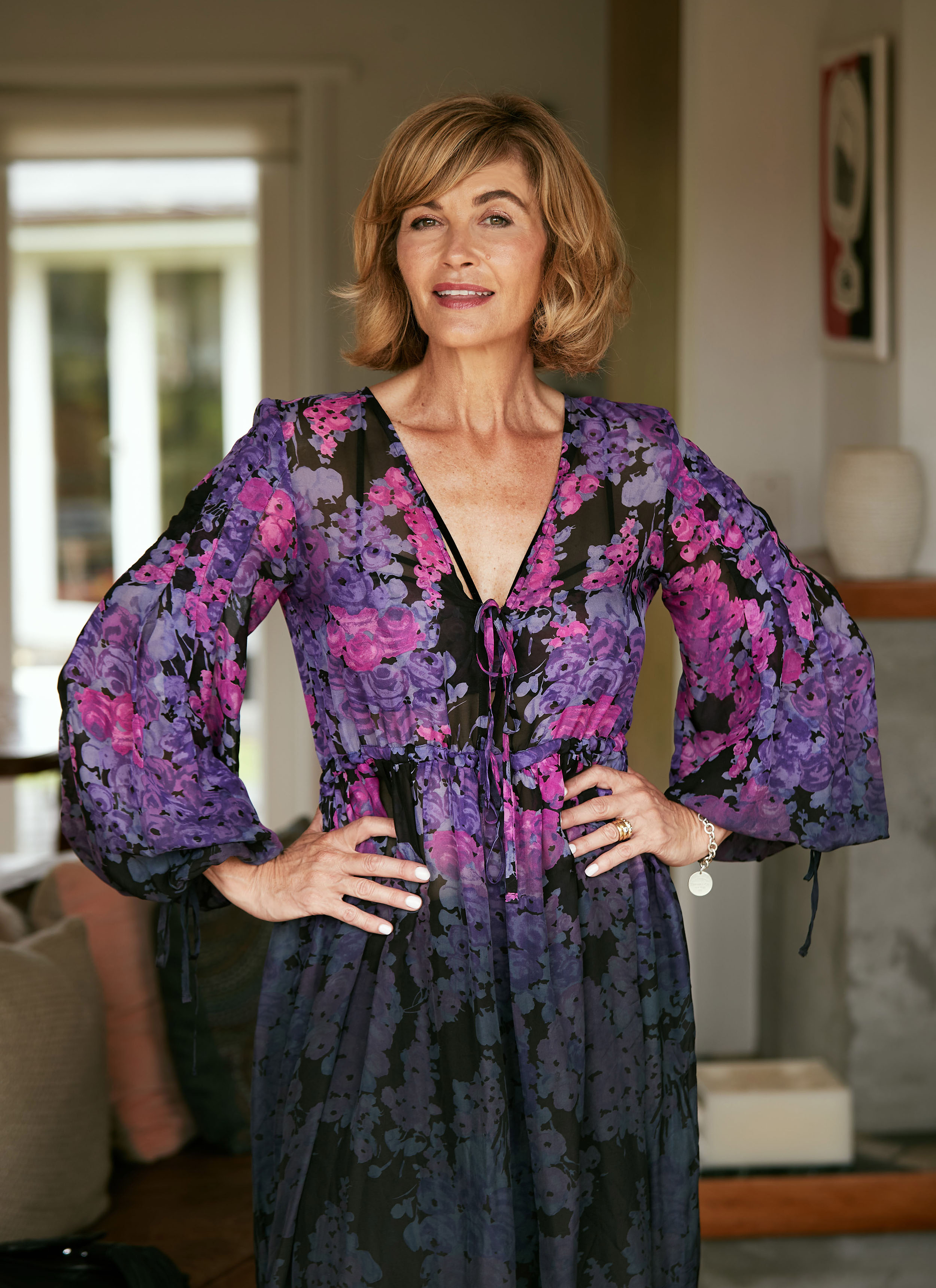 A blonde woman wearing a pink and purple floral dress with hands on hips