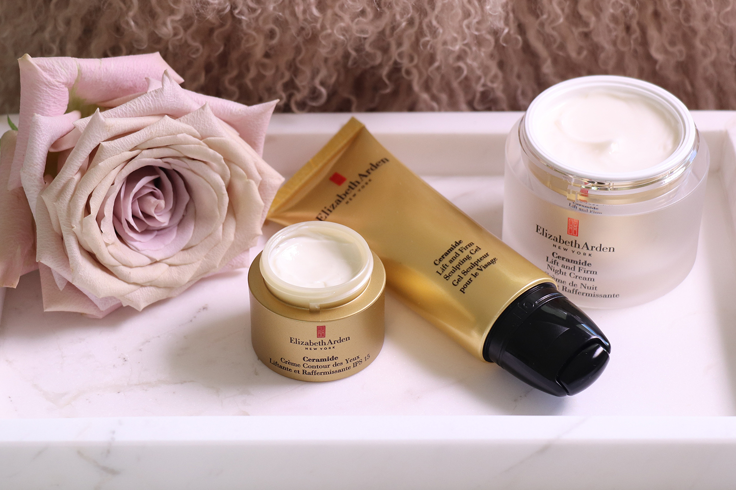 several Elizabeth Arden products in gold bottles laid out on a white bench sitting next to a dusty pink rose