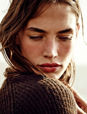 Zoomed in shot of a female model looking down over her shoulder wearing a brown knit cardigan