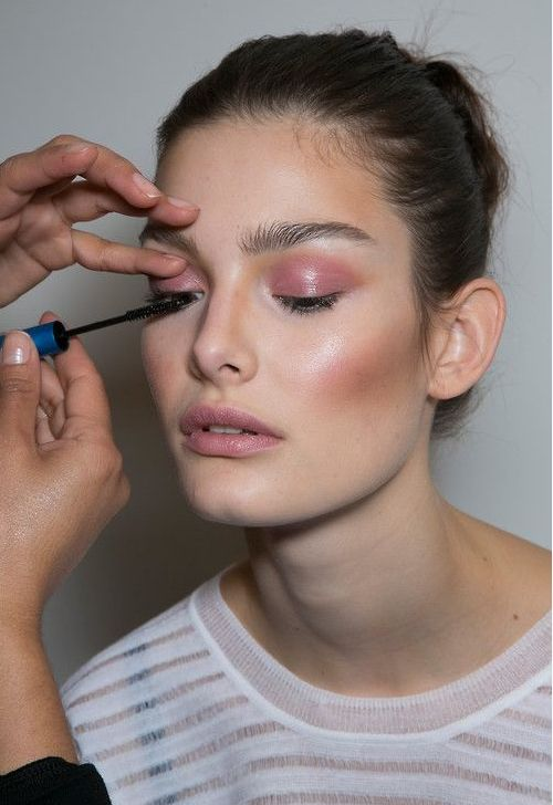 brunette model with pink eyeshadow getting mascara applied to one eye