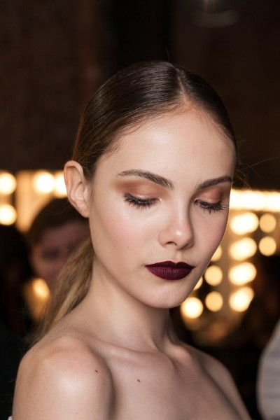 brunette model with bronze eye shadow and dark purple lips with hair pulled back and bare shoulders
