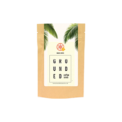 Grounded Mango and Papaya coffee body scrub. A brown paper bag with a white leafy image on it