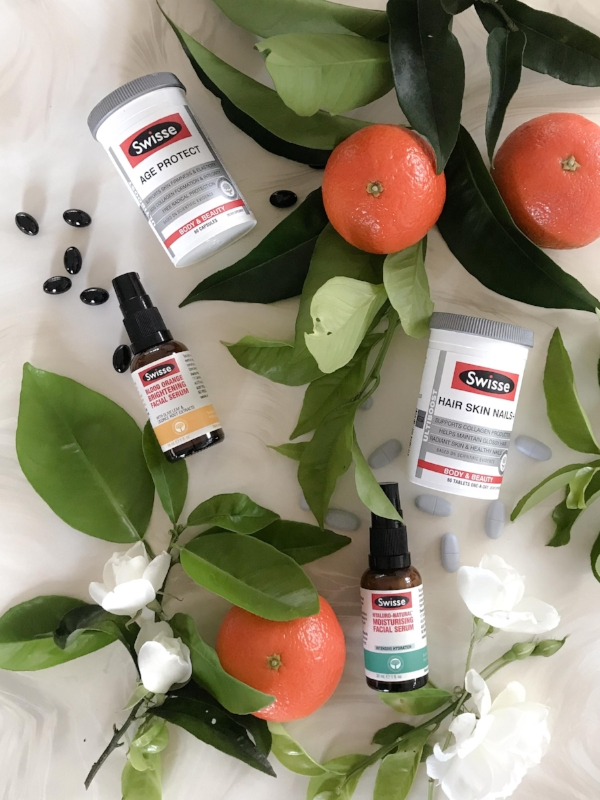 Several Swisse beauty products laid out against a white background surrounded by white flowers, green leaves and tangerines