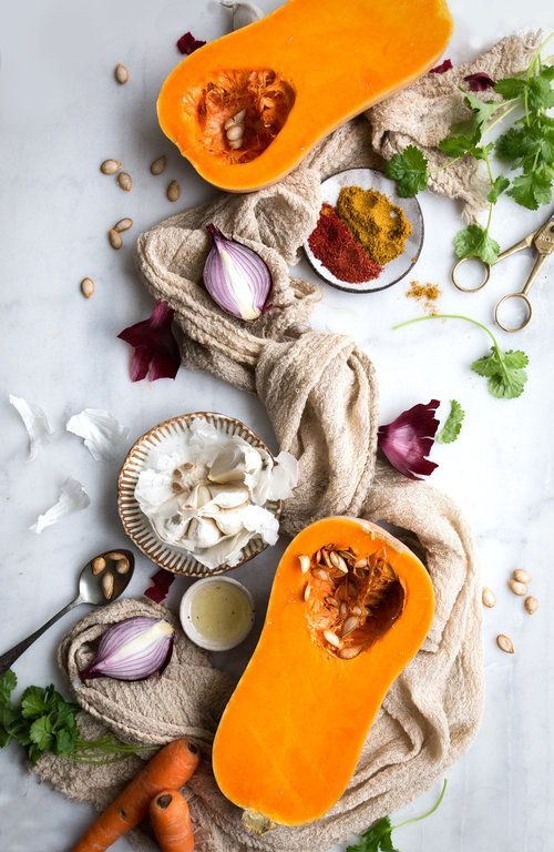 A range of vegetables such as onions, garlic, squash, some coriander and seeds laid out on a white background with against a long cloth