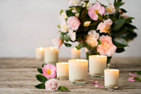 Group of different sized, white Essano candles on a wooden table surrounded by pink flowers