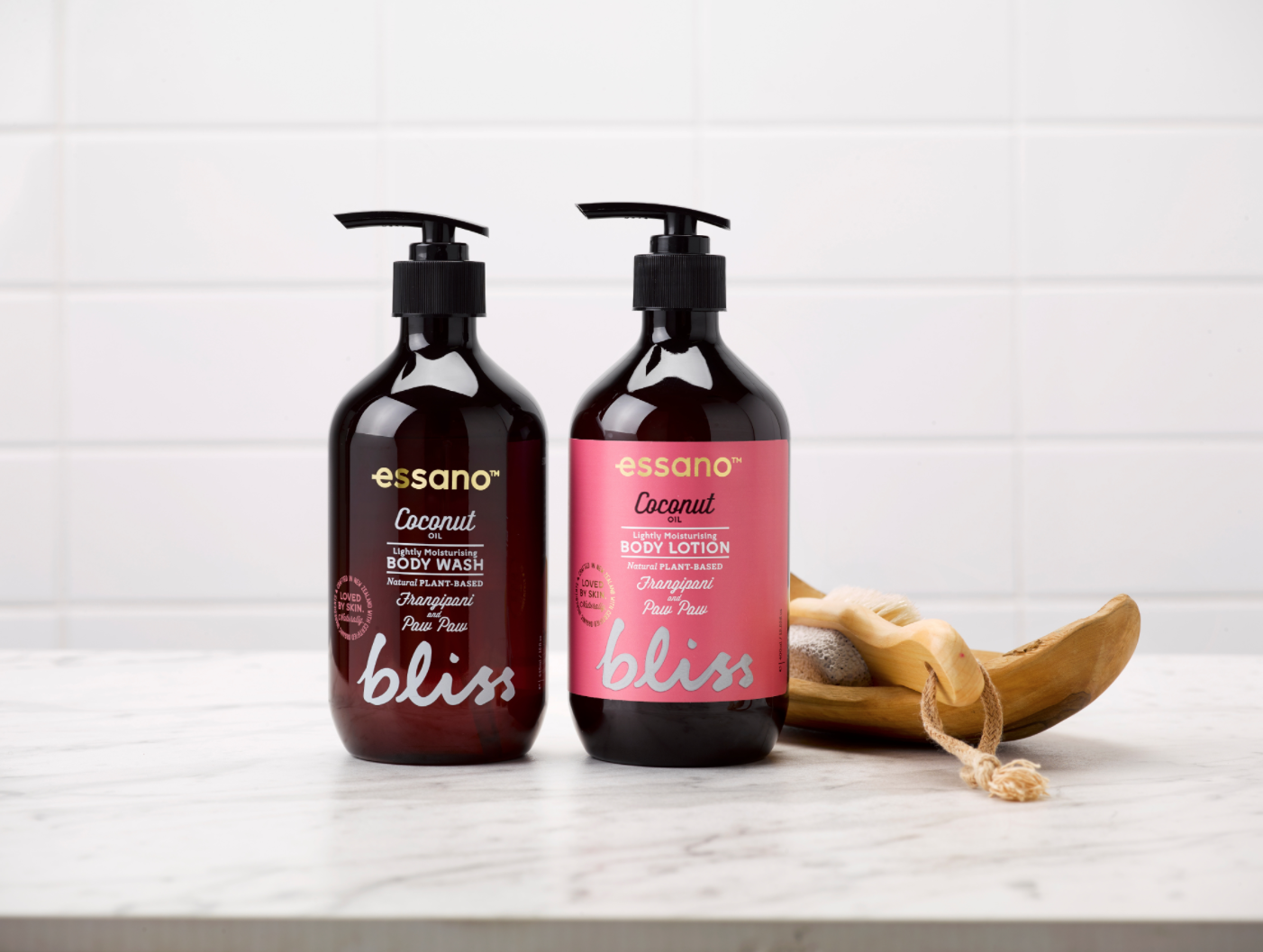 Two Essano bottles sitting on a white bench next to a banana peel and body scrub brush