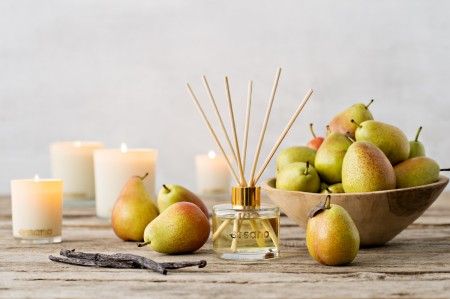 An Essano diffuser on a wooden table surrounded by green pears and lit up Essano candles in the background