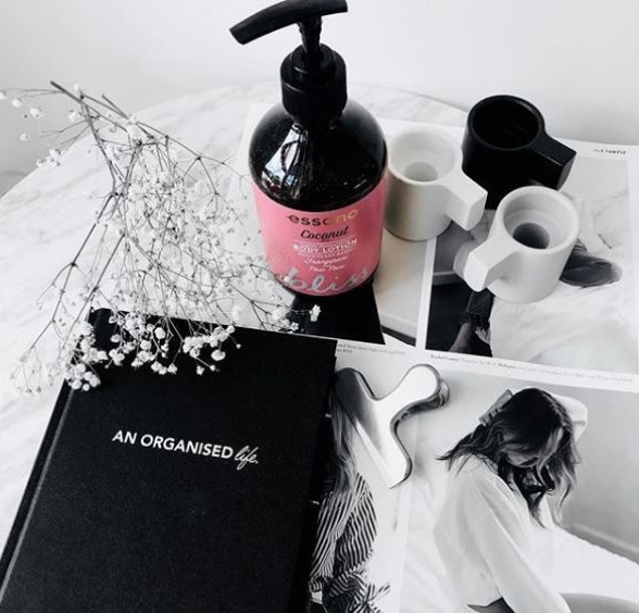 Essano body lotion in pink and brown bottle sitting on a table with various books, flowers and hair clips
