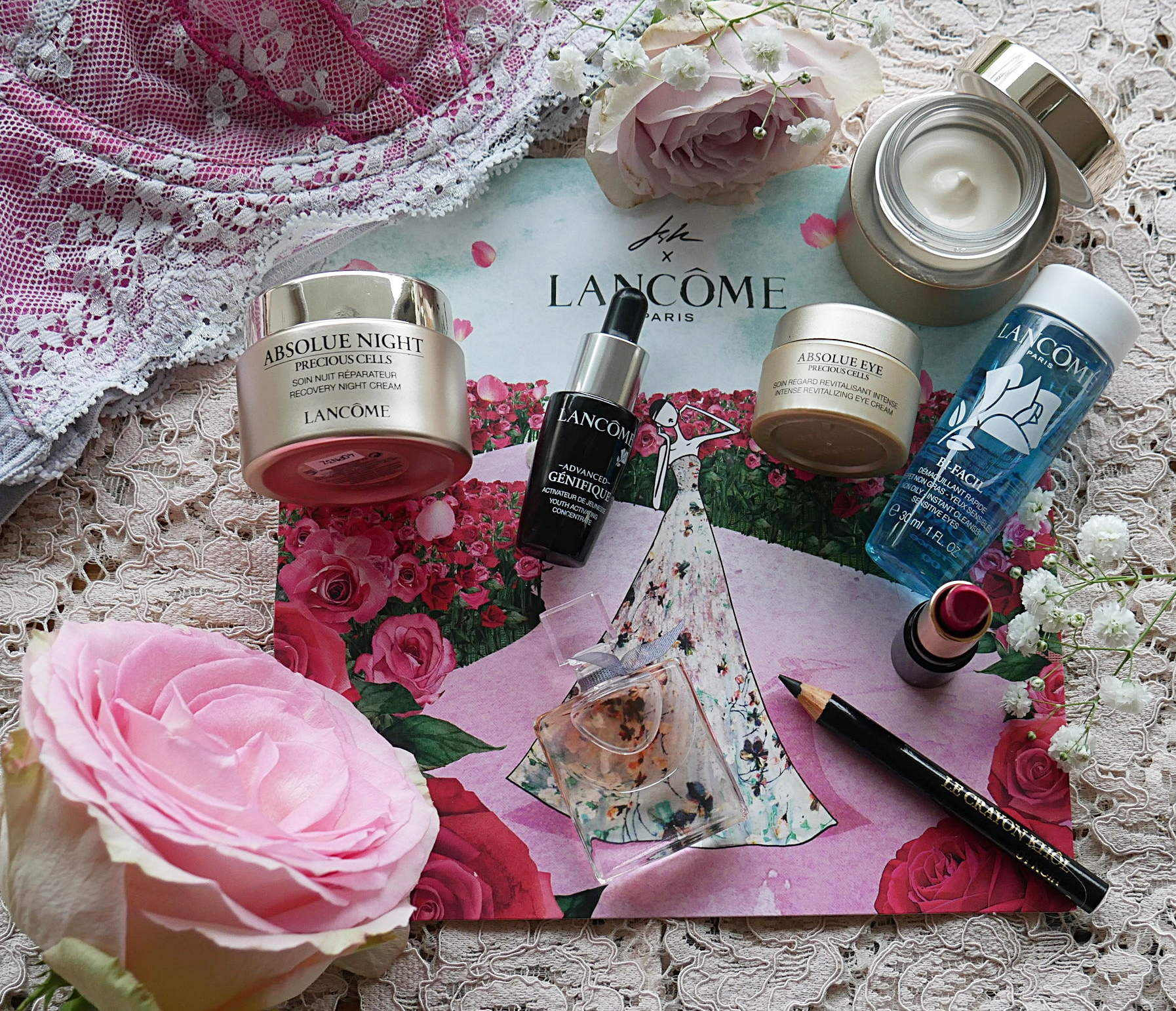 A selection of different Lancome beauty products spread out against a lace floral background , the underwire of a pink bra and a pink flower