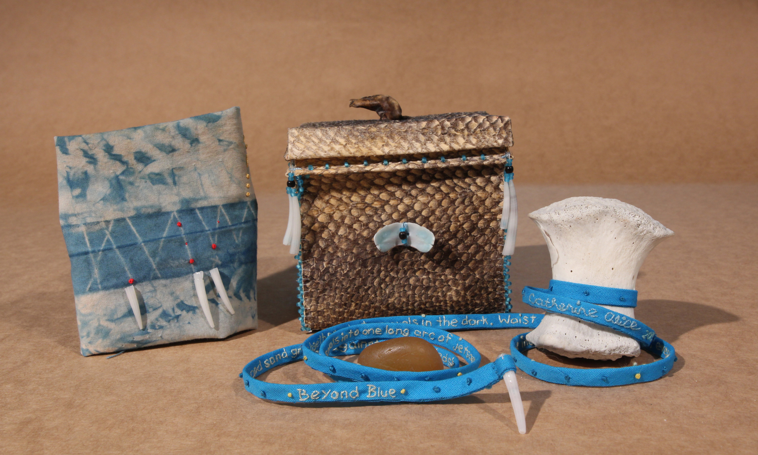 Beyond Blue  , 2016. Embroidered text spooled on a seal's knuckle bone, beaded salmon leather box lined with indigo dyed cotton. Agate and embroidered map on indigo dyed cotton included.