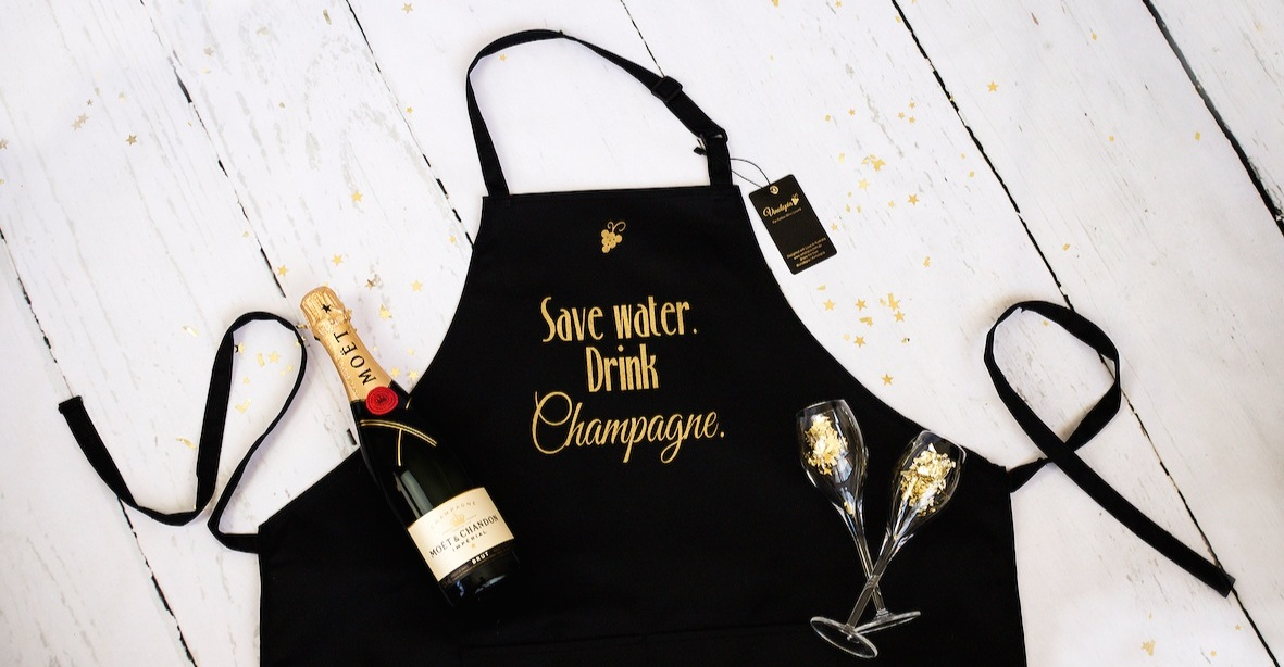 WINELOVER APRONS - One size fits all • Stunning gold heat press print • High quality poly cotton twill • Two front pockets • Adjustable neck straps • Designed by Vinotopia.Wholesale: Multiples of 5.Note: we can do your own custom designs as well (min. order 150 units).