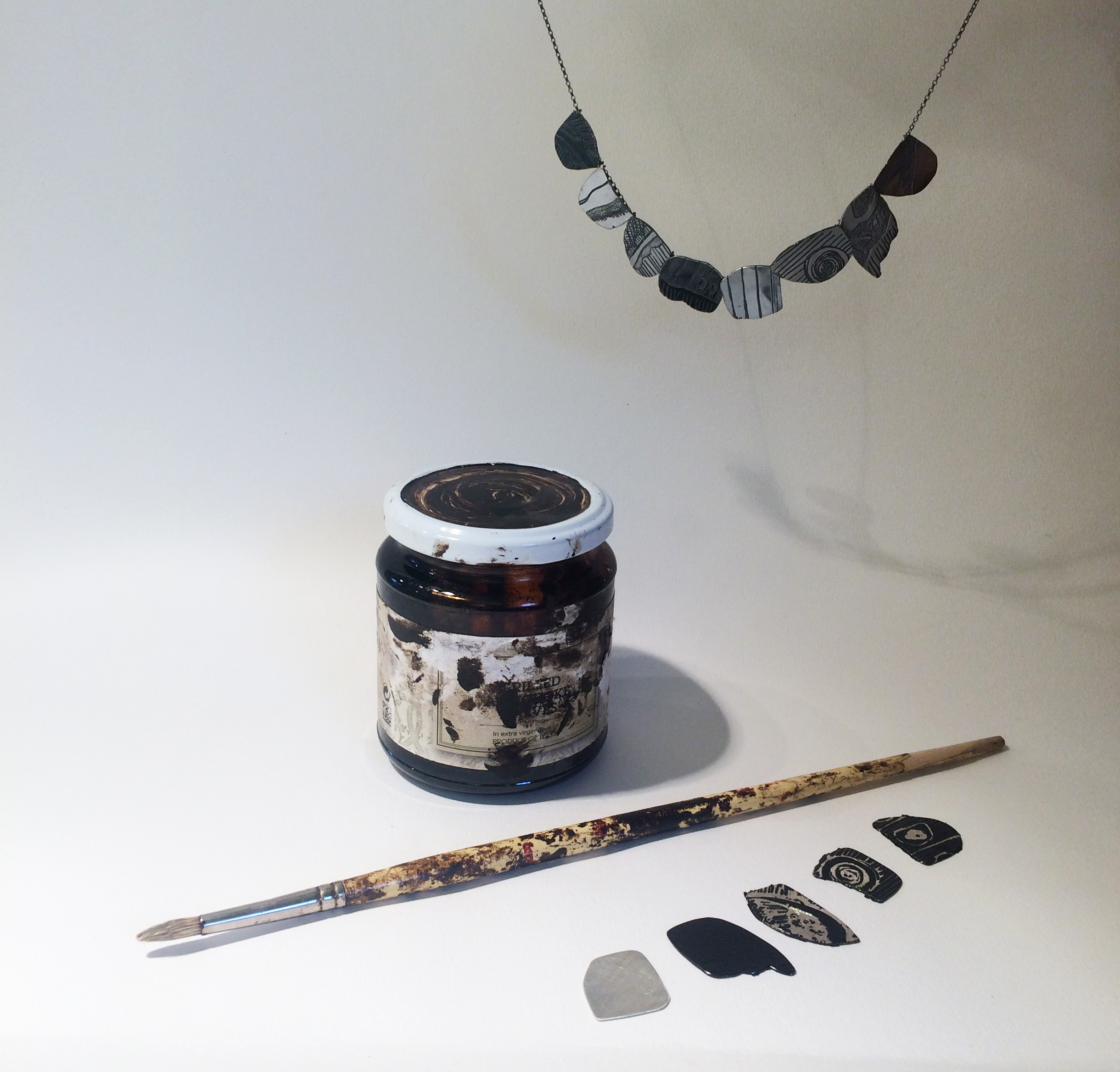 Eden Silver-Myer showing the steps in her etching process and finished necklace in oxidised silver.