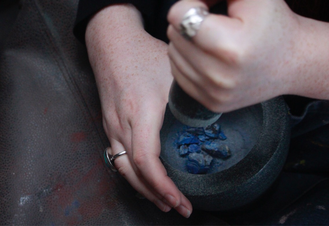 Caitlin crushing precious Lapis Lazuli.