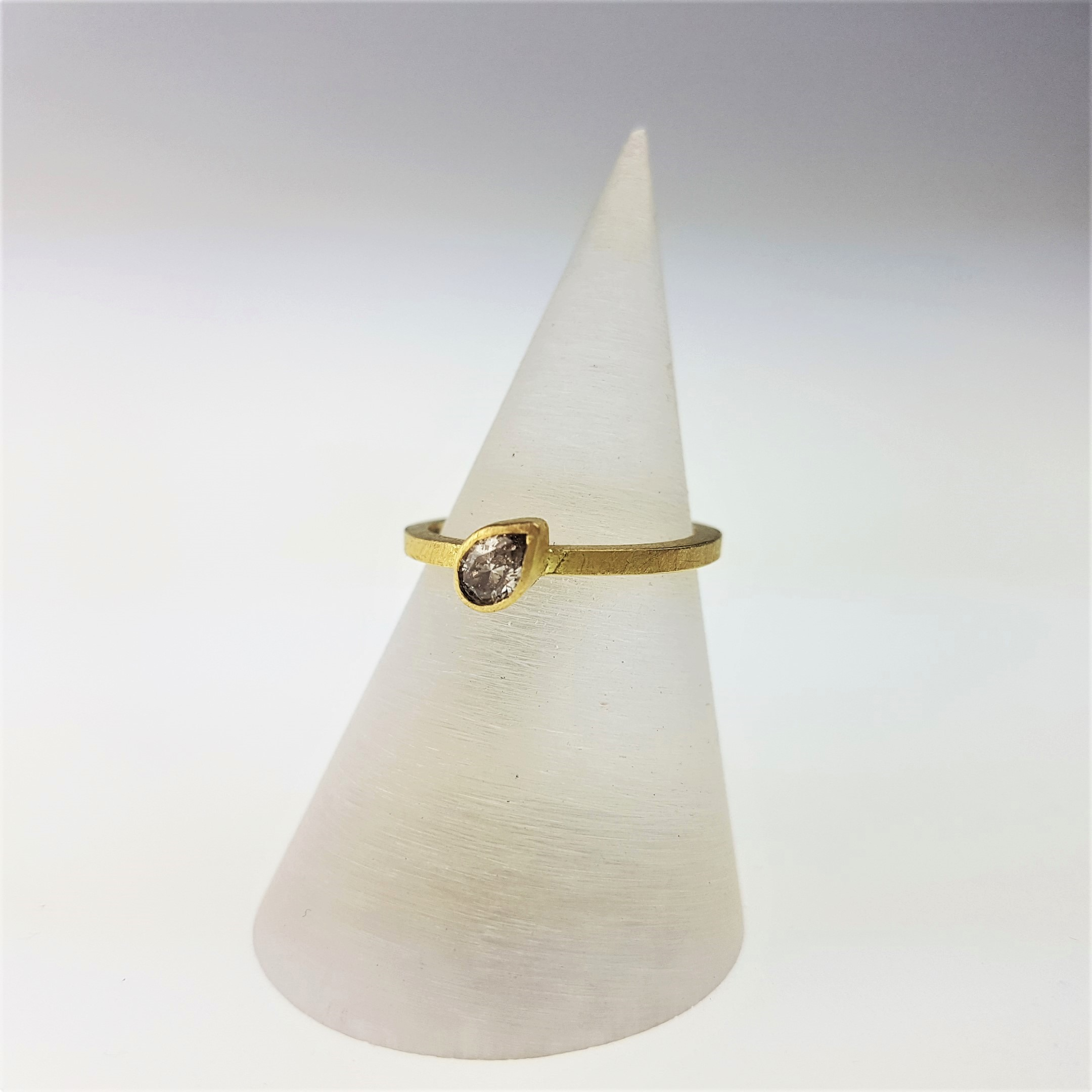 Asymmetry - Our in house goldsmith Rachel Jones completed her masters at The Royal College of Art in 2018 specialising in gold alloys, a true modern alchemist. Specialising in modern luxury, this beautiful pear cut champagne diamond is set at a contemporary angle on a crisp edged 18ct gold band in her signature matt brushed finish, £1100.