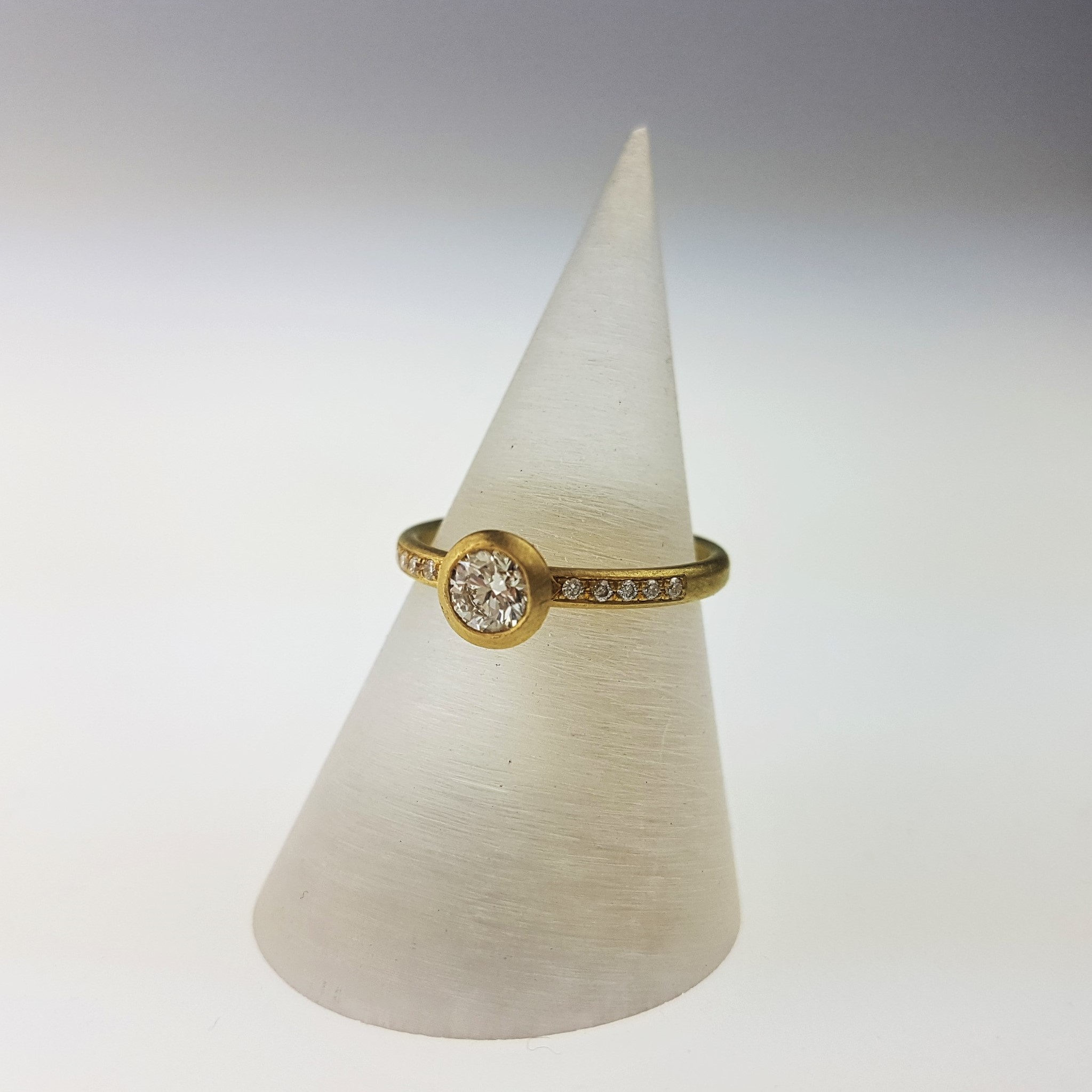 Classic Elegance - This white diamond ring with diamond set shoulders is by Natalie Harris in 18ct yellow gold with a matt finish £2550.