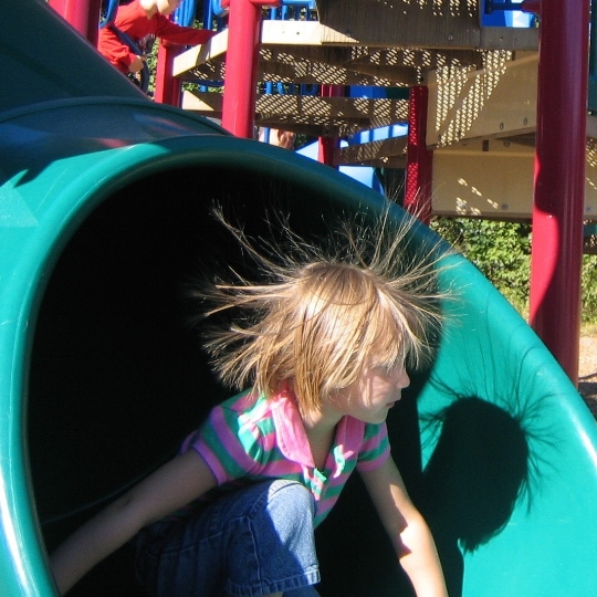 Is this girl a member of the band  The Cure ? No! She looks like that because sliding down a plastic slide rubbed a bunch of electrons off her hair and created static electricity.
