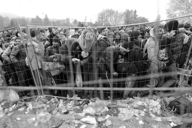 Migrants queue to cross the border in to Austria