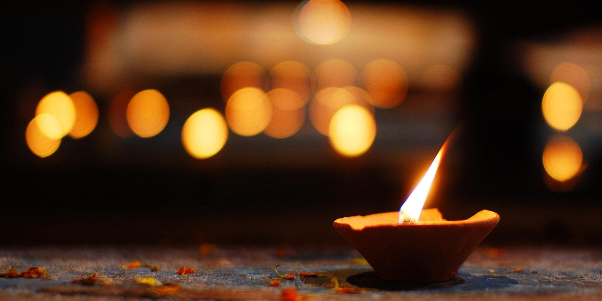single diwali candle. blurred lights in background.jpg