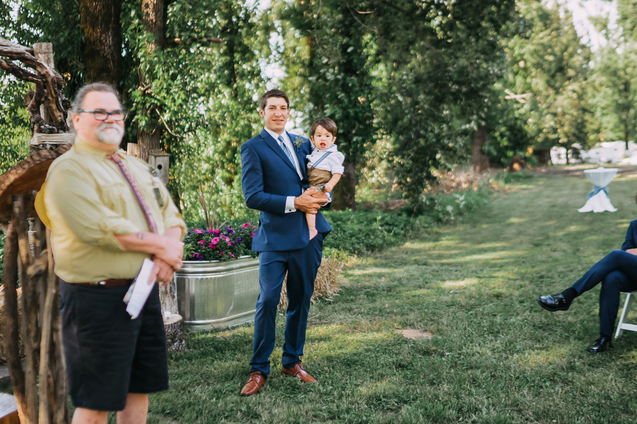 Groom hold son wedding party ceremony at altar Backyard wedding green