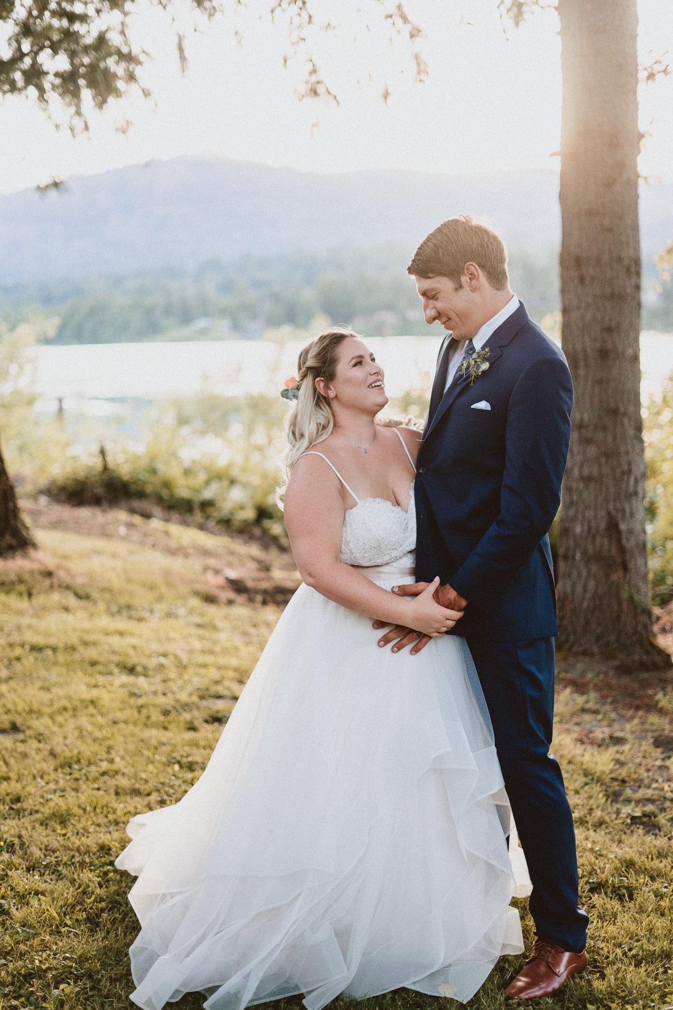 Sunset backlit portrait bride groom blue suit vertical portrait mode