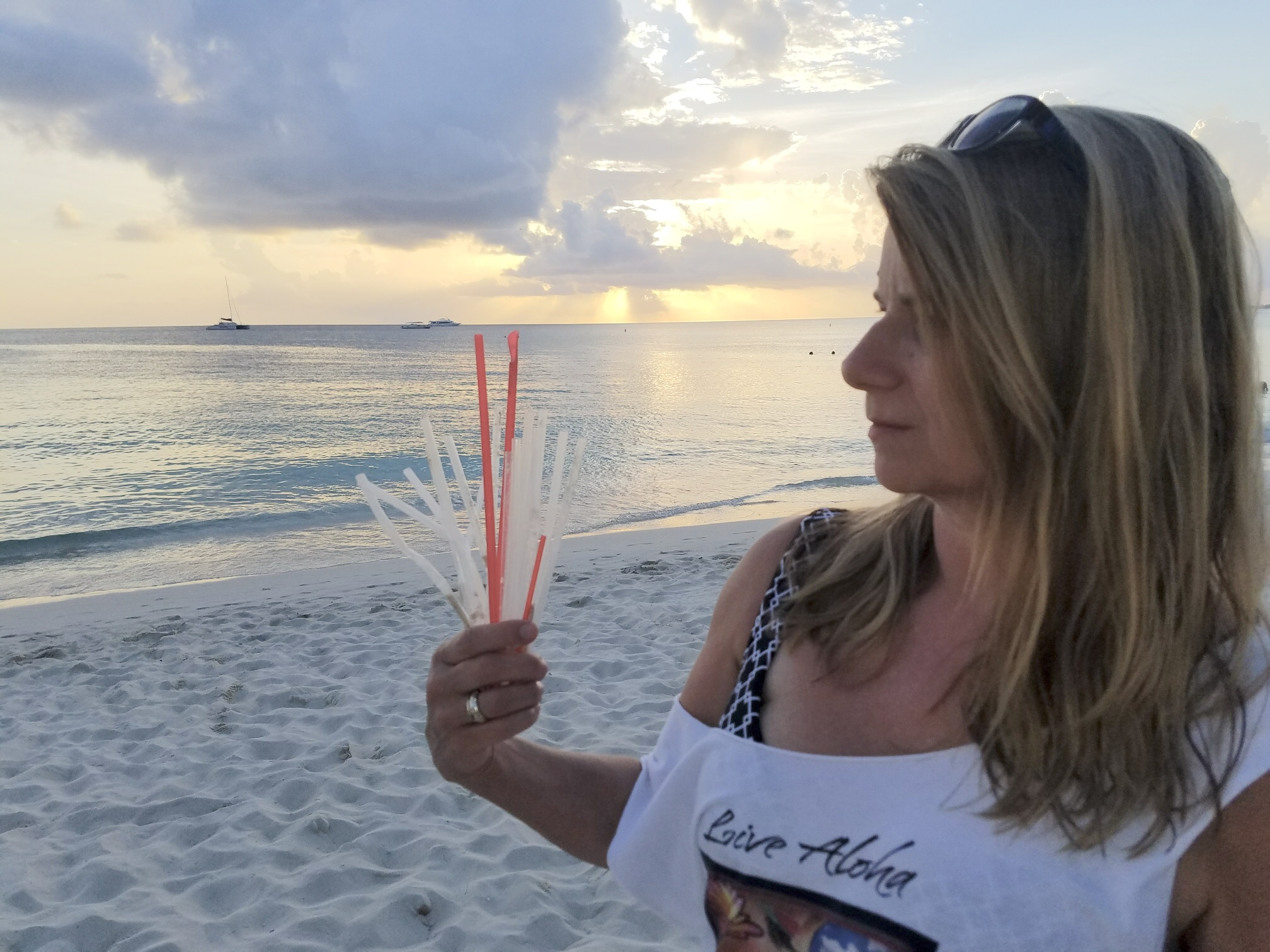 STRAWS Producer/Director Linda Booker and discarded plastic straws on Grand Cayman's 7 mile beach.