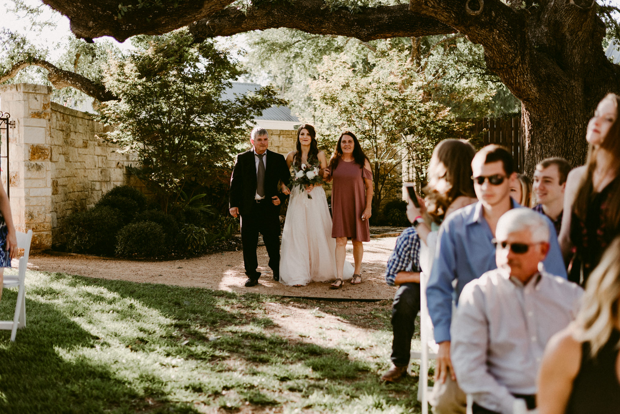 Intimate-Cathedral-Oaks-Wedding-Ceremony-Bride-Walking-Down-The-Aisle--Kerlyn-Van-Gelder-Photography-Austin-Wedding-Photographer