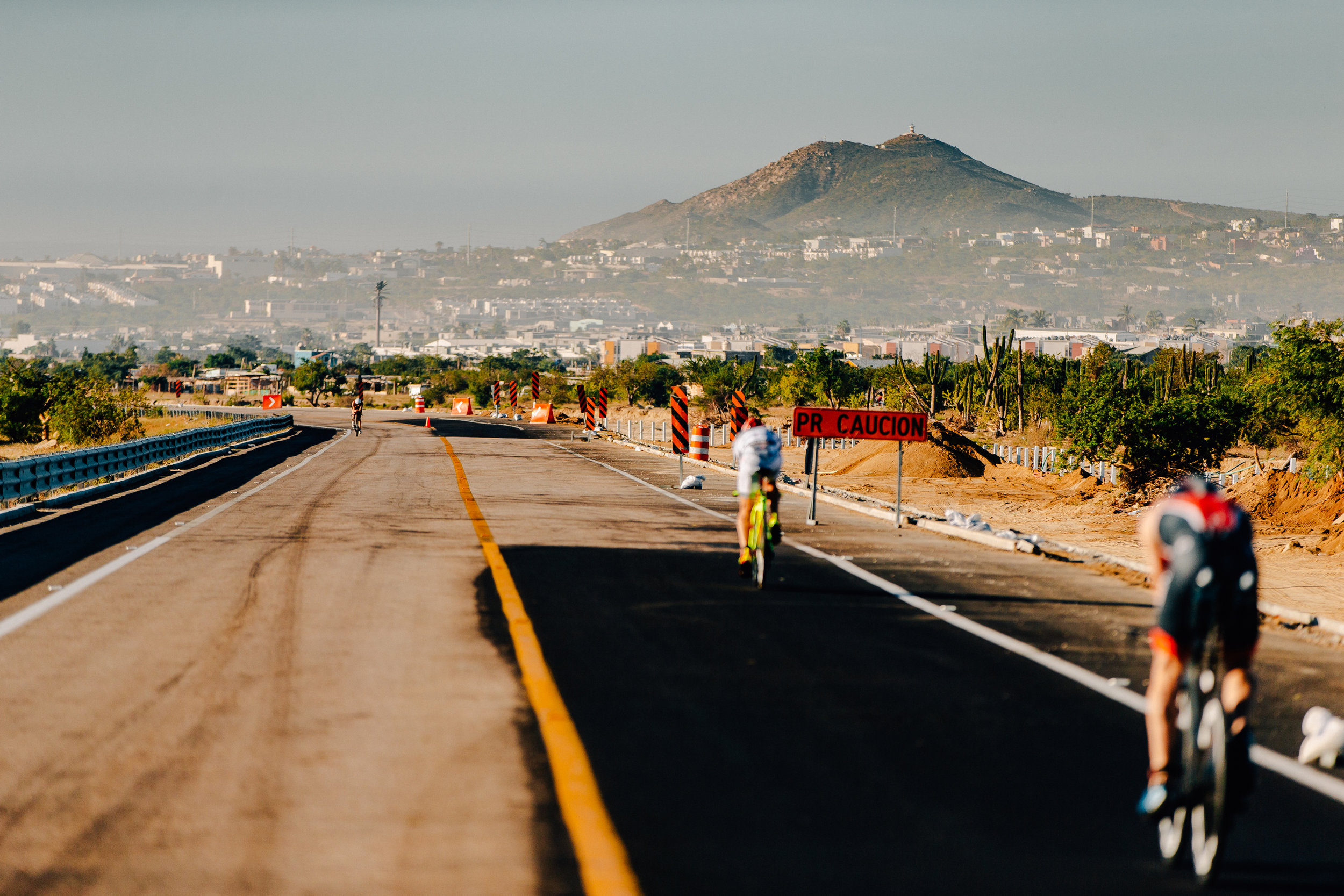 Lauren Brandon heading out on the toll road turn around as the men's chase group heads back into Cabo San Lucas.