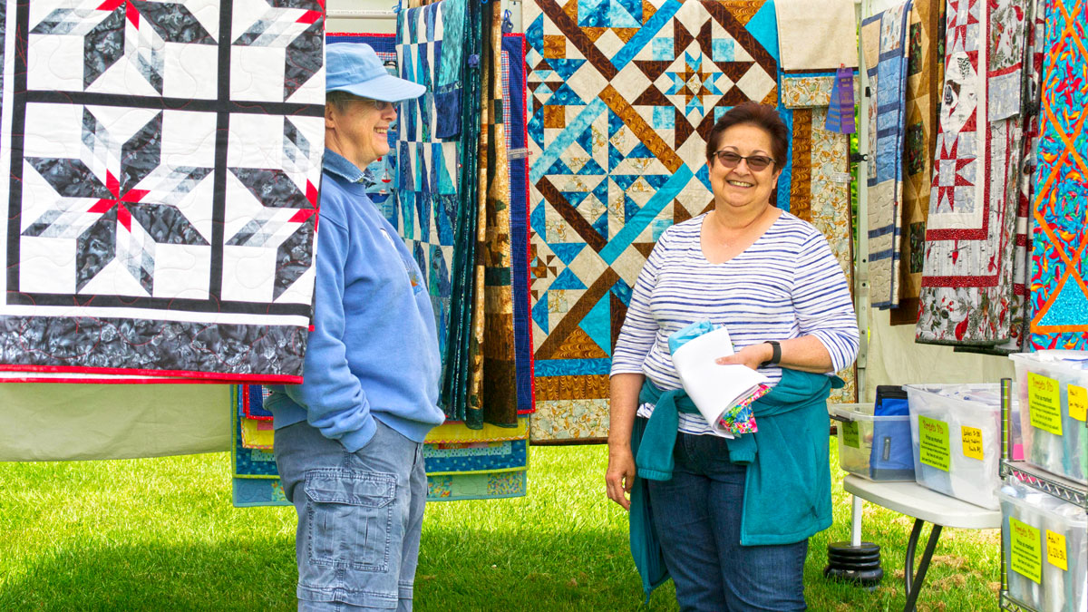 Mary Barstow  (left) shows her quilts at the Saturday Market