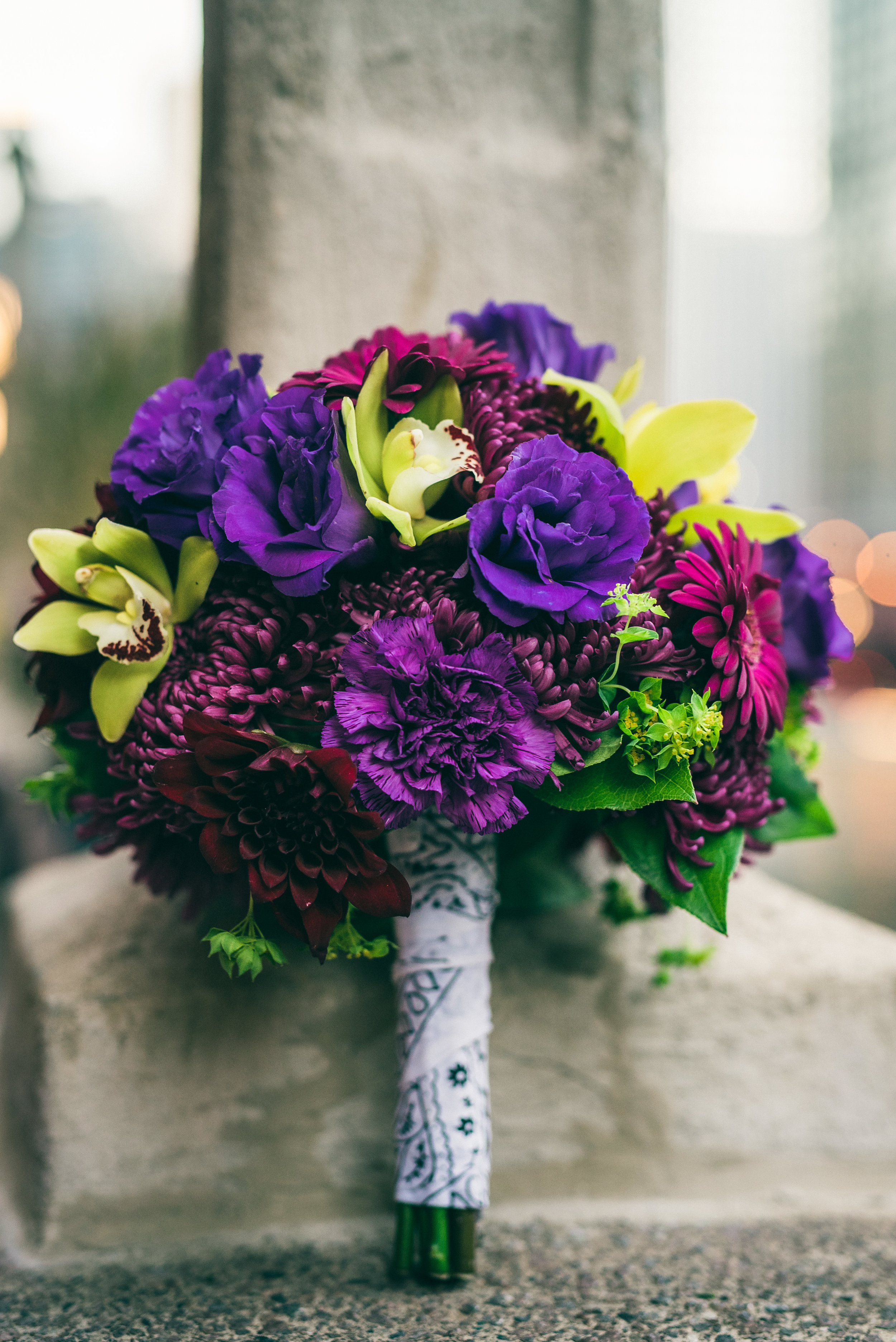 Purple and green bridal bouquet with orchids, lisianthus and dahlias