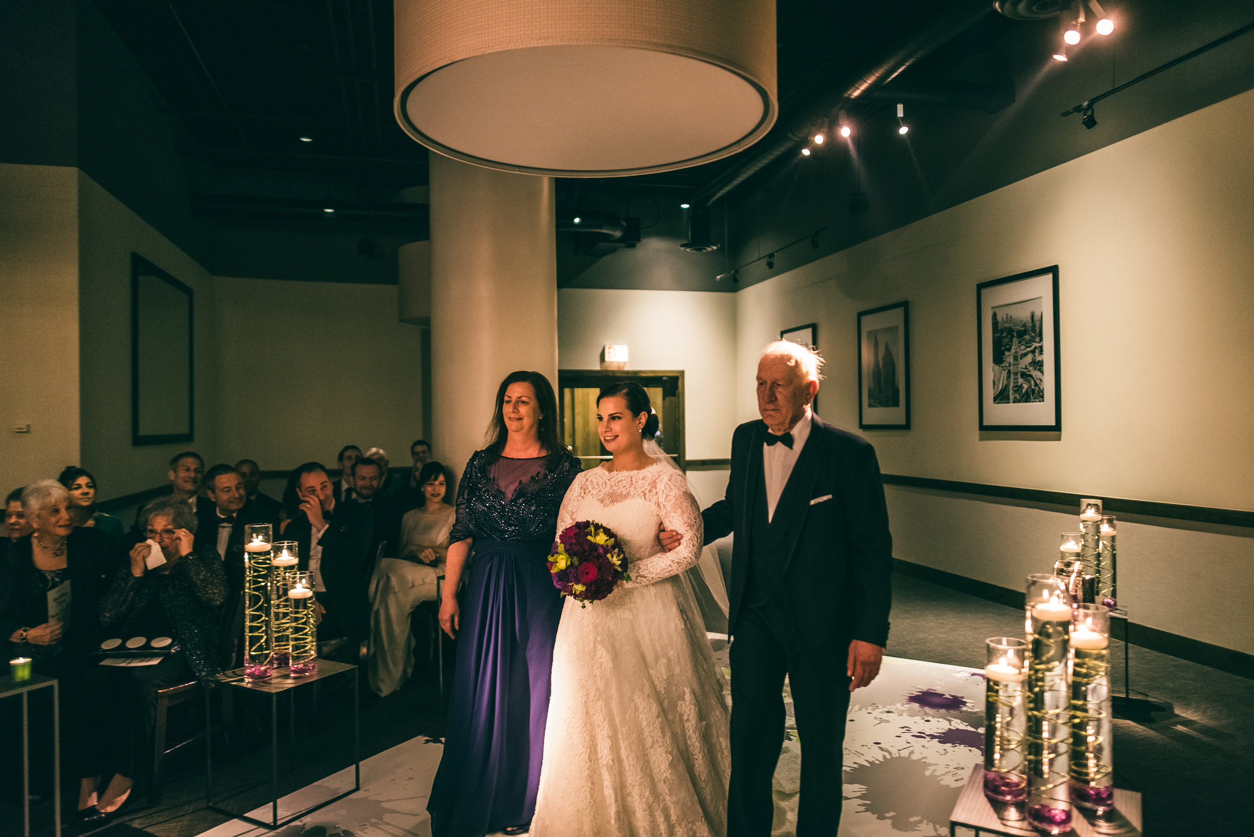 Bride walking down the aisle with her Mother and Father for Jewish ceremony at River Roast Social House in Chicago