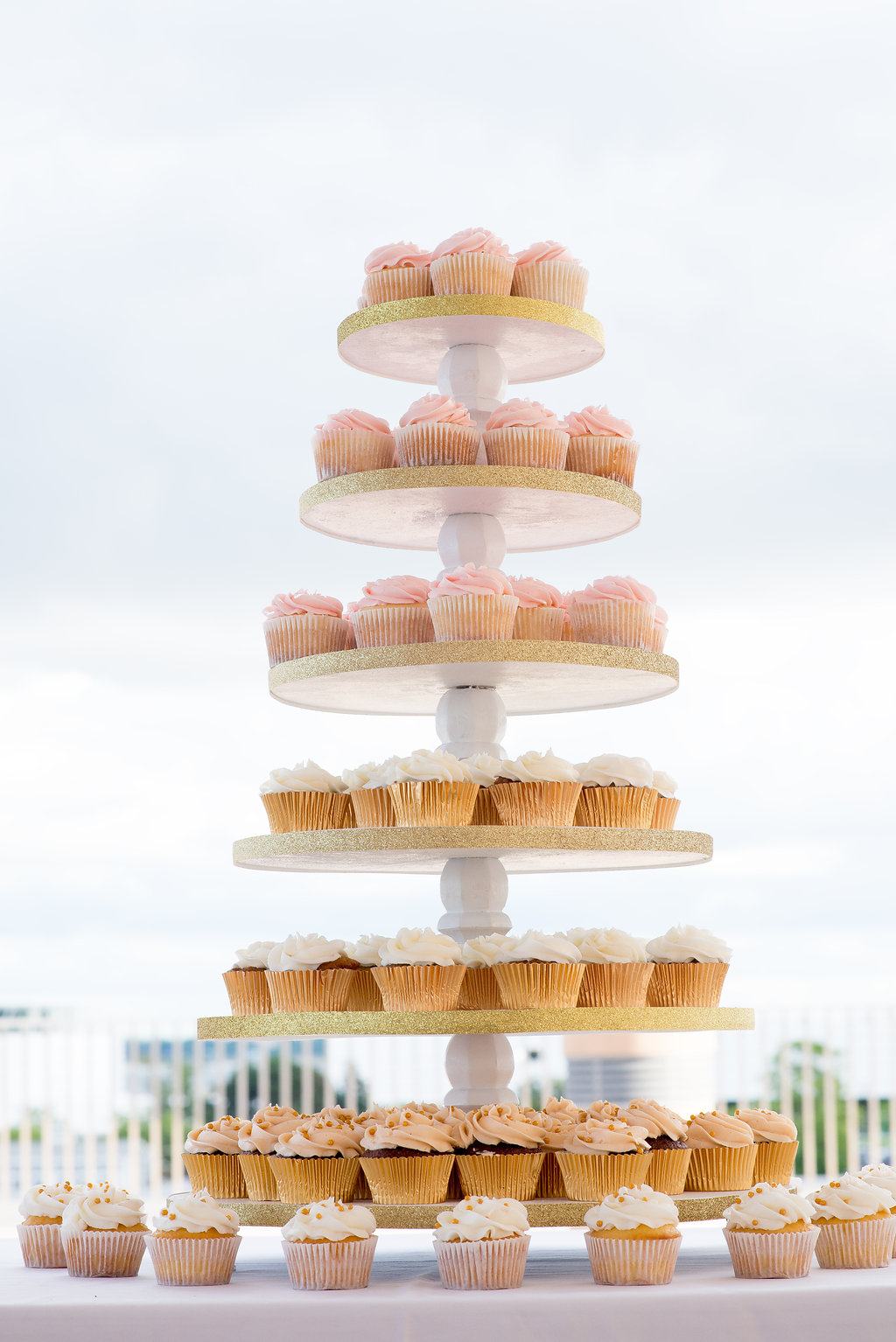Blush and gold cupcake display for wedding reception dessert table