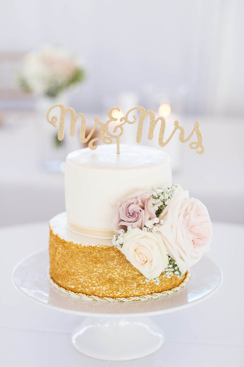 White and gold two tier wedding cake with blush roses