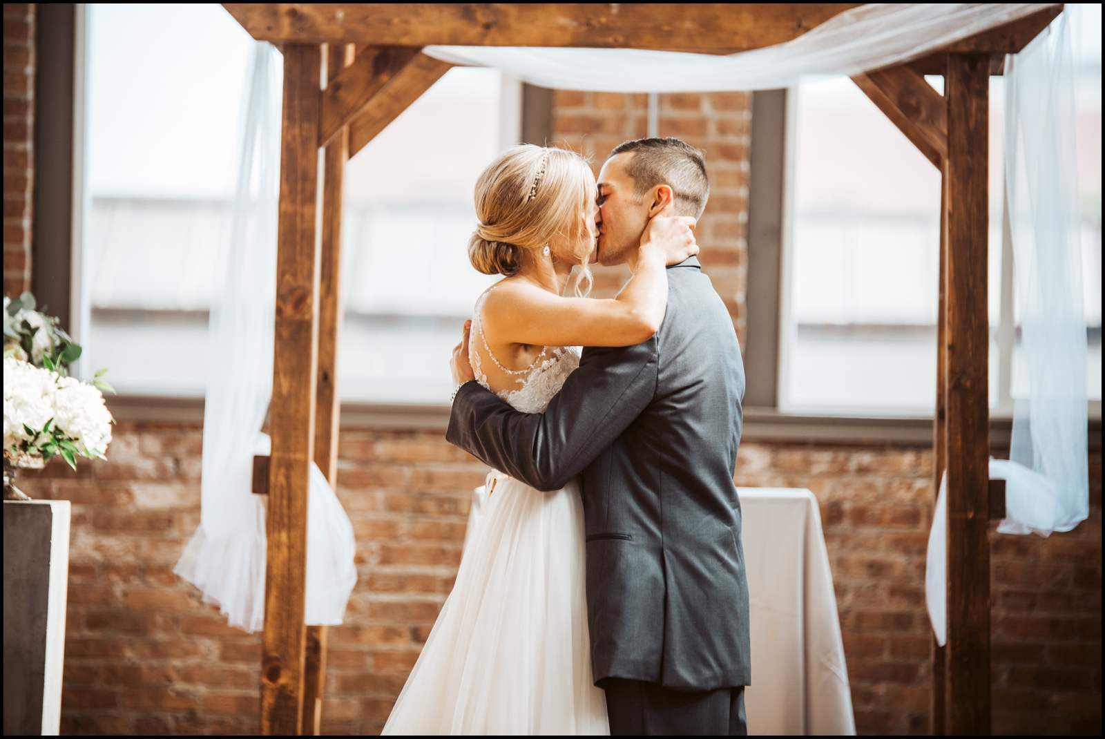 Bride and groom kiss during their ceremony